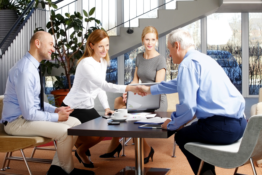 High angle view business group. Businesswoman sitting at meeting and shaking hands with senior businessman. Teamwork at office.